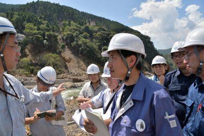 ダム予定地で被災状況の説明を受ける田村議員(中央)ら=23日、熊本県南阿蘇村
