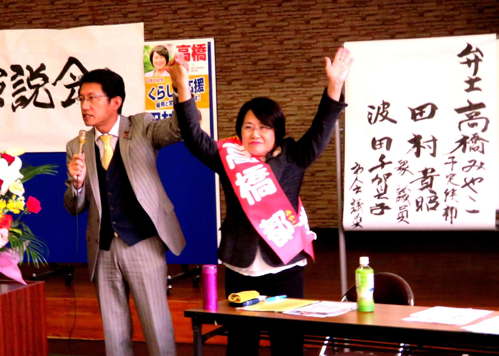 高橋都市議候補と手を上げて、参加者に支援を呼びかける田村貴昭衆院議員=3日、北九州市