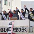 拍手に手をあげてこたえる(左から)やない、藤沢、市田、大石、出口各氏=21日、北九州市