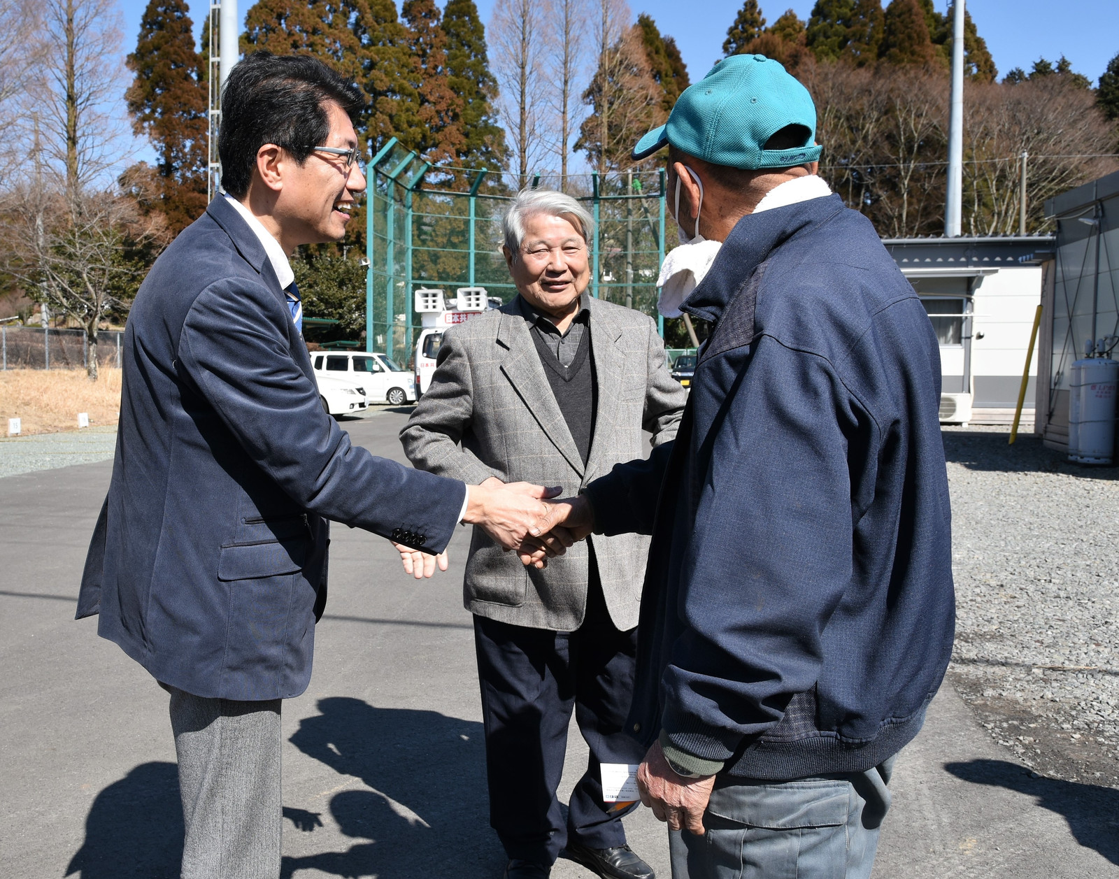 仮設入居者から激励される(左から)田村、立石の両氏=19日、熊本県南阿蘇村