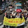 (横断幕左から)吉田、伊波、田村、荒木各氏を先頭にデモ行進する参加者ら=19日、福岡市