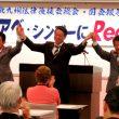 手をあげて参加者の拍手に応える左から田村、真島、仁比の各国会議員=4月28日、北九州市