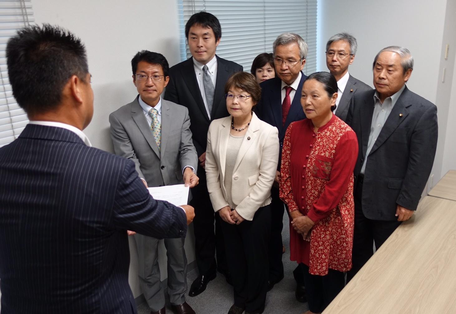 担当者に申し入れ書を渡す田村(向かって左端)、山下(その後ろ)両候補ら=2日、福岡市