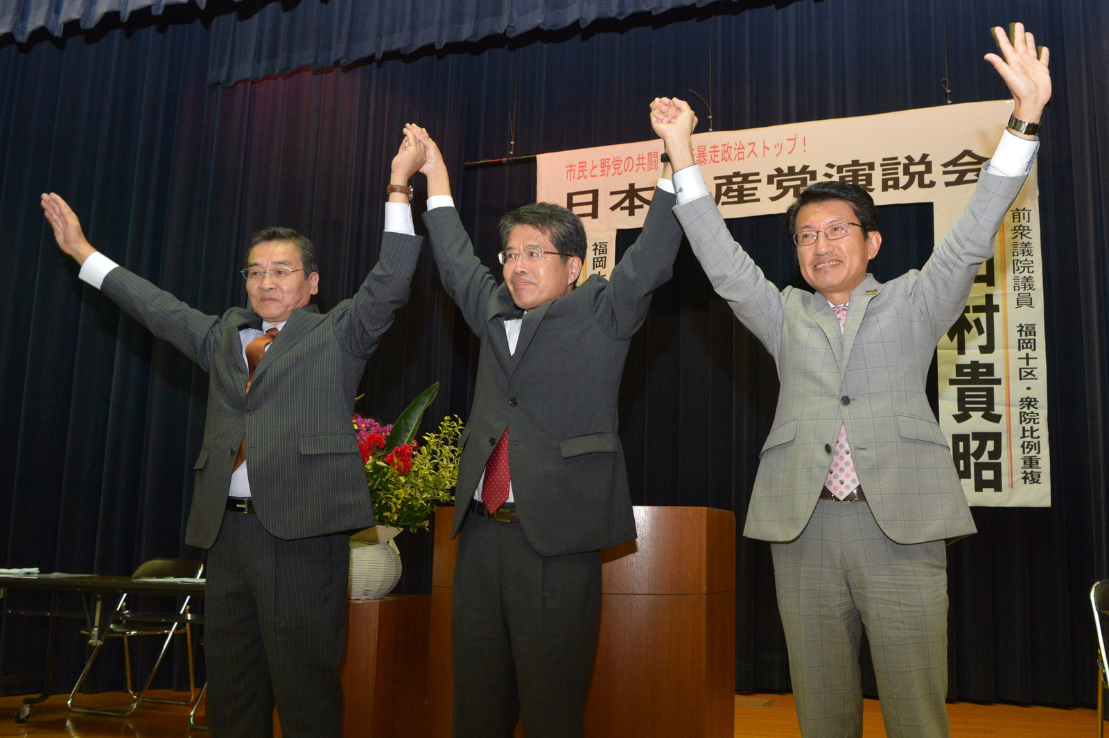 拍手に応える(右から)田村、たけうち、高橋各候補=7日、福岡県苅田町