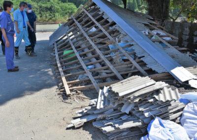 アスベストを含んだ屋根材を確認する(左から)田村、まじまの両氏ら=22日、熊本県人吉市