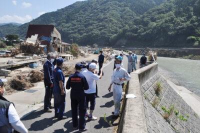 かさ上げした堤防を乗り越えて水が押し寄せた現場を確認する調査団=2日、熊本県八代市坂本町